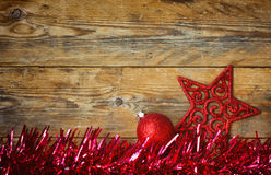 Christmas background with tinsel, red ball, star carved royalty free stock photography
