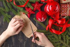 Christmas background. Top view of kid hands wrap New Year present. Packed gifts and scrolls, spruce branches and tools on shabby w Royalty Free Stock Image