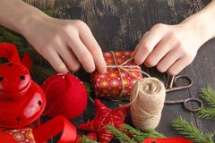 Christmas background. Top view of kid hands wrap New Year present. Packed gifts and scrolls, spruce branches and tools on shabby w Royalty Free Stock Photo