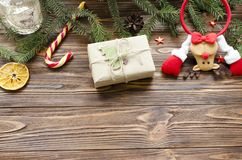 Christmas background: toy deer, gift box, fir, candy on wooden table.  Royalty Free Stock Images