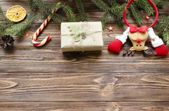 Christmas background: toy deer, gift box, fir, candy on wooden table.  Royalty Free Stock Image
