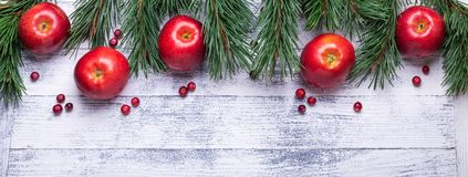 Christmas background with tree branches, red apples and cranberries. Dark wooden table royalty free stock image