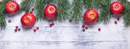 Christmas background with tree branches, red apples and cranberries. Light wooden table. Snowfall drawing effect royalty free stock image