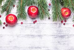 Christmas background with tree branches, red apples and cranberries. Light wooden table. Snowfall drawing effect stock photos
