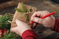 Christmas background. view of hands writing on gift box. Packed. Gifts and scrolls, spruce branches on shabby wooden table. Workplace for preparing handmade new Stock Images