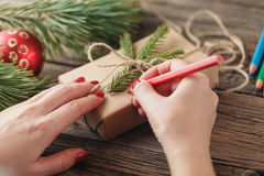 Christmas background. view of hands writing on gift box. Packed Royalty Free Stock Photo