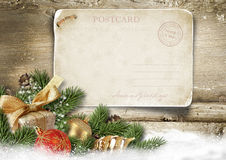 Christmas background with vintage postcard, ball, fir on wood Royalty Free Stock Photo