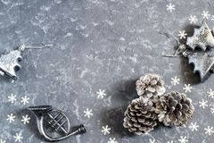 Christmas background with vintage silver Christmas toys and cone. S. Christmas and New Year concert. Festive decorations and confetti snowflakes on grey concrete Stock Image