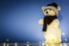 Christmas background, wallpaper with toy polar bear. Blue Christmas background, wallpaper, with standing polar bear puppet, string lights, with copy space Stock Photography