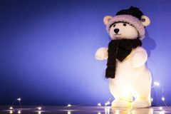 Christmas background, wallpaper with toy polar bear. Blue Christmas background, wallpaper, with standing polar bear puppet, string lights, with copy space Stock Photo