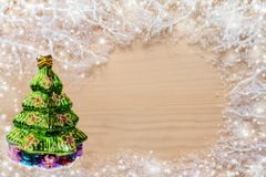 White frosty branches with snow, green glass Christmas tree and copy space on natural uncolored wooden background. royalty free stock images