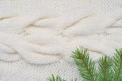 Christmas background white knitting pattern and spruce branches Royalty Free Stock Images