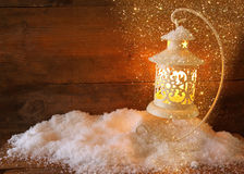 Christmas background with white lantern and snow over wooden background. Royalty Free Stock Images