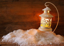 Christmas background with white lantern and snow over wooden background Stock Images