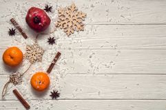 Christmas background. White rustic table with tangerines, cinnamon sticks, anise-star, wooden snowflakes, artificial snow. royalty free stock image