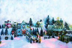 Christmas background of winter miniature scenery with kids. Kid gospel choir singing and reads bible in the middle of Christmas village. Winter fairytale stock photography