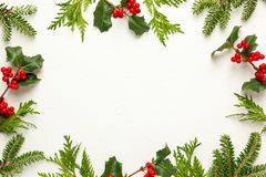 Free Christmas Background With Branches Of Fir Tree, Evergreens And Holly With Red Berries On White. Winter Nature Concept. Flat Lay, Royalty Free Stock Photos - 159766508