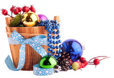 Christmas background with wood bucket, cones, color balls and be Stock Photos