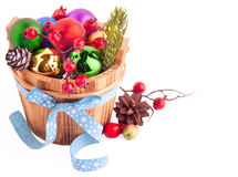 Christmas background with wood bucket, cones, color balls and be Royalty Free Stock Photos