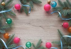 Christmas background on wood with fir twigs, colorful trinkets a Stock Photos