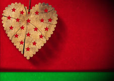 Christmas Background. Wooden heart with stars hanging on red and green velvet background with shadows Royalty Free Stock Photography