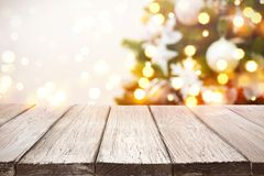 Christmas background. Wooden planks over blurred holiday tree lights.