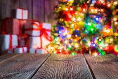 Christmas background with wooden table, light bokeh and presents. Stock Image