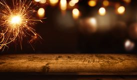 Christmas background with wooden table and sparkler