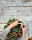 Christmas background with Christmas wreath. And handsl over wood Royalty Free Stock Image