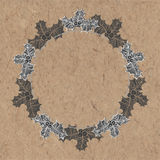 Christmas background with a wreath of holly on kraft paper. Can Royalty Free Stock Image