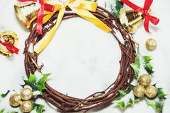 Christmas background, Wreath woven from the branch of the vine with golden bells and green leaf Royalty Free Stock Photo