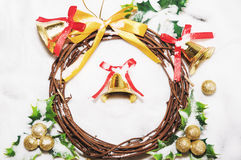 Christmas background, Wreath woven from the branch of the vine with golden bells and green leaf Stock Photos