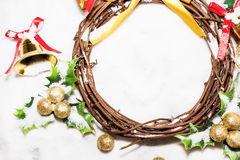 Christmas background, Wreath woven from the branch of the vine with golden bells and green leaf with golden ball Royalty Free Stock Photography