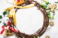 Christmas background, Wreath woven from the branch of the vine with golden bells and green leaf with golden ball Royalty Free Stock Images