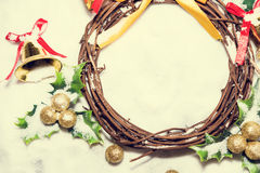 Christmas background, Wreath woven from the branch of the vine with golden bells and green leaf, vintage tone Stock Images