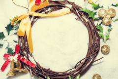 Christmas background, Wreath woven from the branch of the vine with golden bells and green leaf, vintage tone Stock Photos