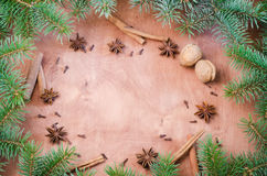 Christmas background for Xmas postcard. Cinnamon sticks, anise stars and cloves on wooden background. Royalty Free Stock Photography