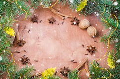 Christmas background for Xmas postcard. Cinnamon sticks, anise stars and cloves on wooden background. Drawn snow. Royalty Free Stock Photography