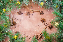 Christmas background for Xmas postcard. Cinnamon sticks, anise stars and cloves on wooden background. Drawn snow. Stock Image