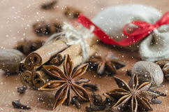 Christmas background for Xmas postcard. Cinnamon sticks, anise stars and cloves on wooden background. Drawn snow. Royalty Free Stock Images
