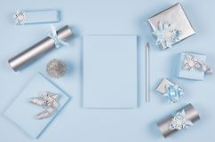 Christmas background for your design and text - blank paper and silver pencil, soft pastel blue and gift boxes with bows. stock photography