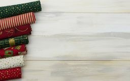 CHRISTMAS BACKGROUNDS. PATCHWORK CLOTH BORDER AGAINST WHITE WOO. DEN DESK OR TABLE stock photo