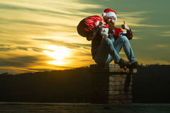 Christmas bad santa on chimney. Young handsome bearded bad santa claus man with long beard in checkered shirt jeans and red new year hat in christmas or xmas Stock Image