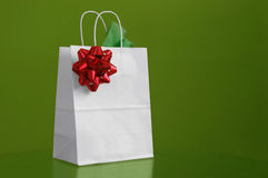 Christmas Bag. A white christmas bag with red bow in green background Royalty Free Stock Photo