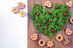 Christmas bake background with paper copy space. Cookies and heart of twigs aside stock photography