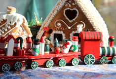 Christmas baked sweet houses and red train. Christmas baked sweet houses and toy train with funny passengers Stock Image