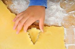 Christmas baking. Hand of a child holding a cookie cutter, flattended dough and flour on the table Stock Photo