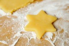 Christmas baking. Dough star and flour on table Stock Photos