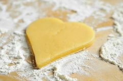 Christmas baking. Dough heart and flour on table Royalty Free Stock Photography
