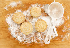 Christmas baking. Home made mince pies on a scratched wooden table covered with icing sugar, next to sieve and metal teaspoon royalty free stock photos